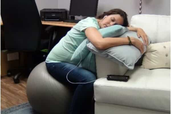 Pregnant student listening to hypnosis on birth ball