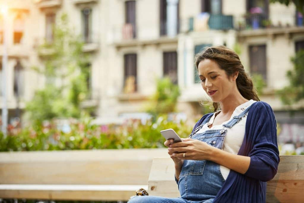 Pregnant woman wearing overalls, sitting on a bench and looking at her phone.