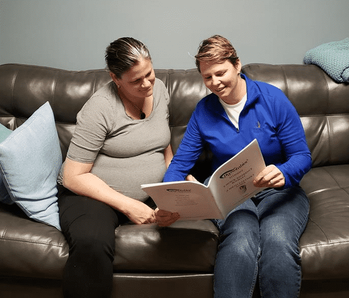 Hypno-mom Melinda and her partner sitting on a leather sofa and reading from the Quick Reference Booklet.