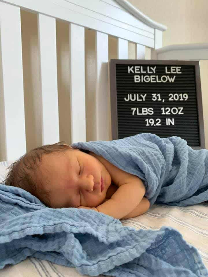 Hypno-baby Kelly wrapped in a blue blanket in a crib with a sign saying Kelly Lee Bigelow July 31, 2019 7lbs 12 oz 19.2 in.