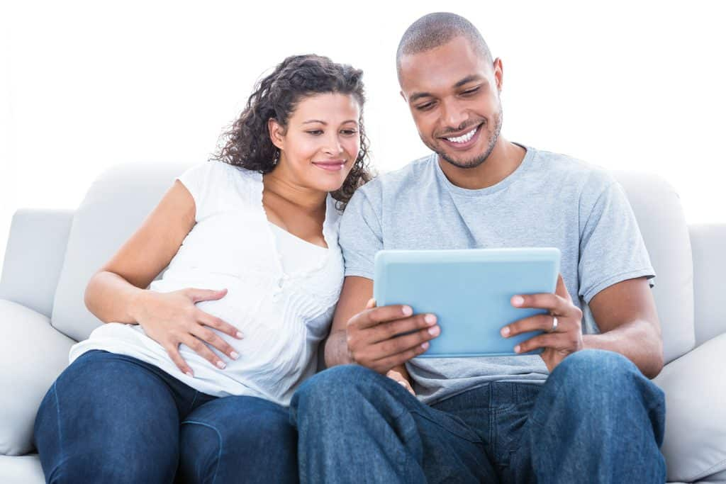 Pregnant woman with her hand on her tummy sitting next to her partner on a grey couch looking at a tablet and smiling..