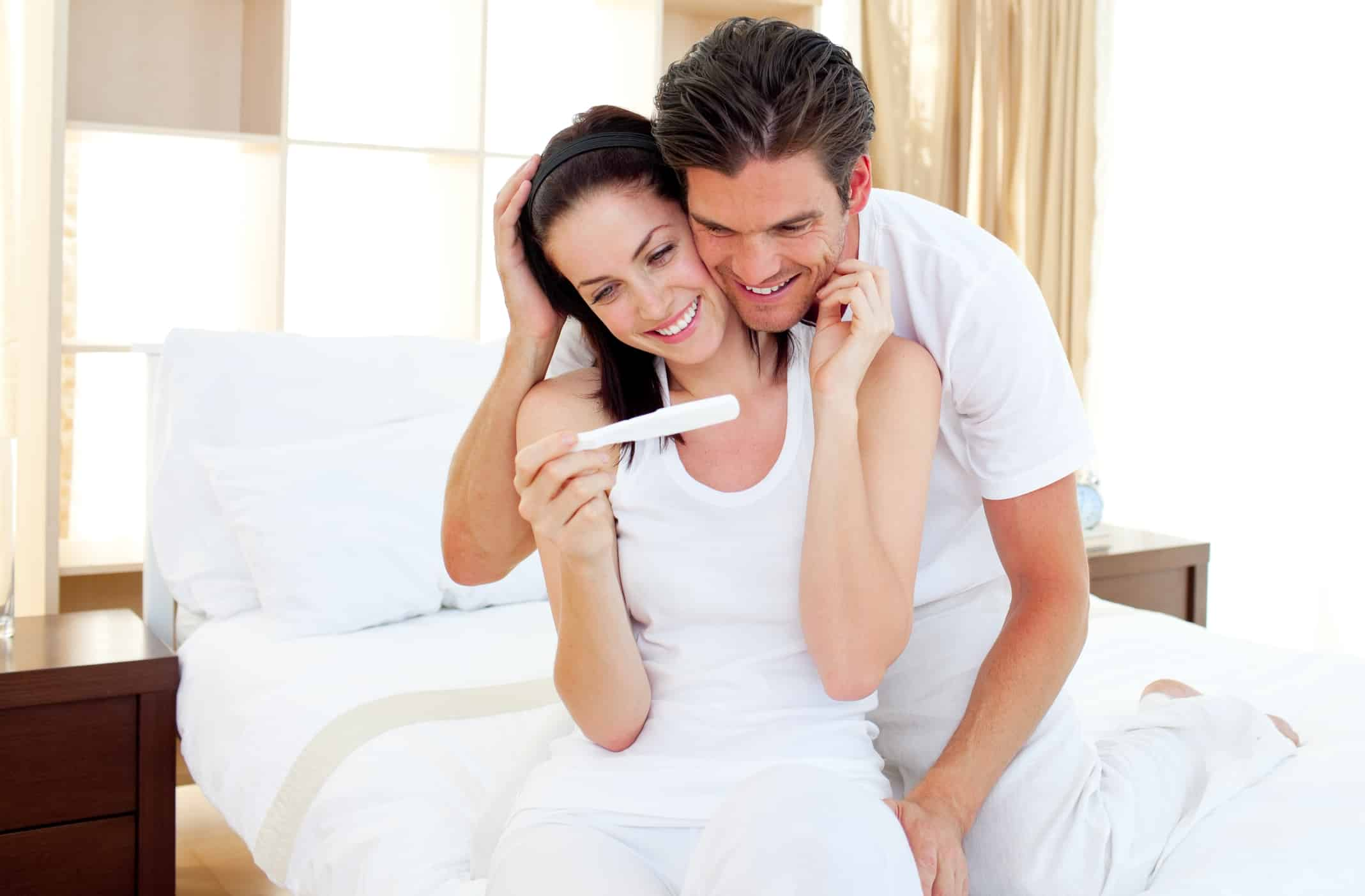 Caucasian couple all in white smiling and holding a pregnancy test.