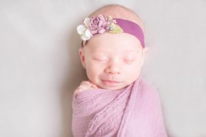 Hypno-mom Brooke's newborn baby wrapped in pink blanket with flowered headband.