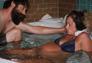 Hypno-mom lying back in birth tub wearing headphones with birth partner's hand on her shoulder