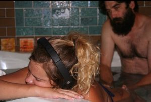 Hypno-mom wearing headphones in kneeling in tub with partner providing counter pressure on hips