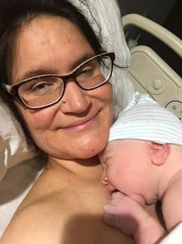 Hypno-mom skin to skin with newborn and smiling at the camera