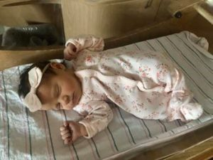 newborn baby in sleeper laying in bassinet with bow on her head