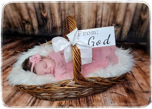 Baby in a basket with a pink bow and blanket and a sign that says from God