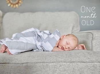 one month old baby laying on chair with a grey striped blanket