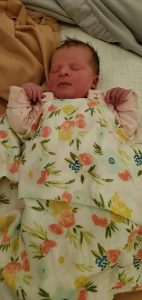 Newborn baby covered in a floral blanket