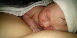 Close up of newborn baby on parent's chest