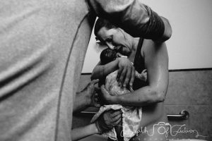 Black and white photo immediately after a waterbirth kneeling in tub holding baby while midwife and birth partner assist