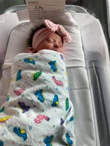 Newborn baby is hospital bassinet swaddled and wearing a big bow.