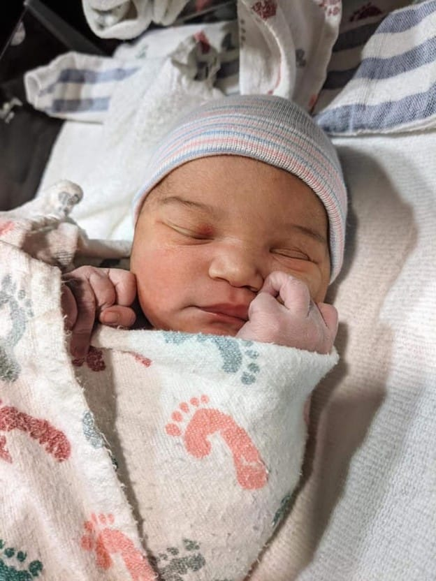 Newborn baby in a swaddle blanket