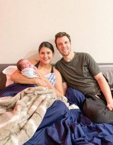 Parent sitting in bed with newborn baby
