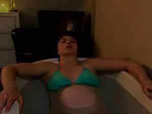 Birthing mom in tub wearing bikini top and relaxing
