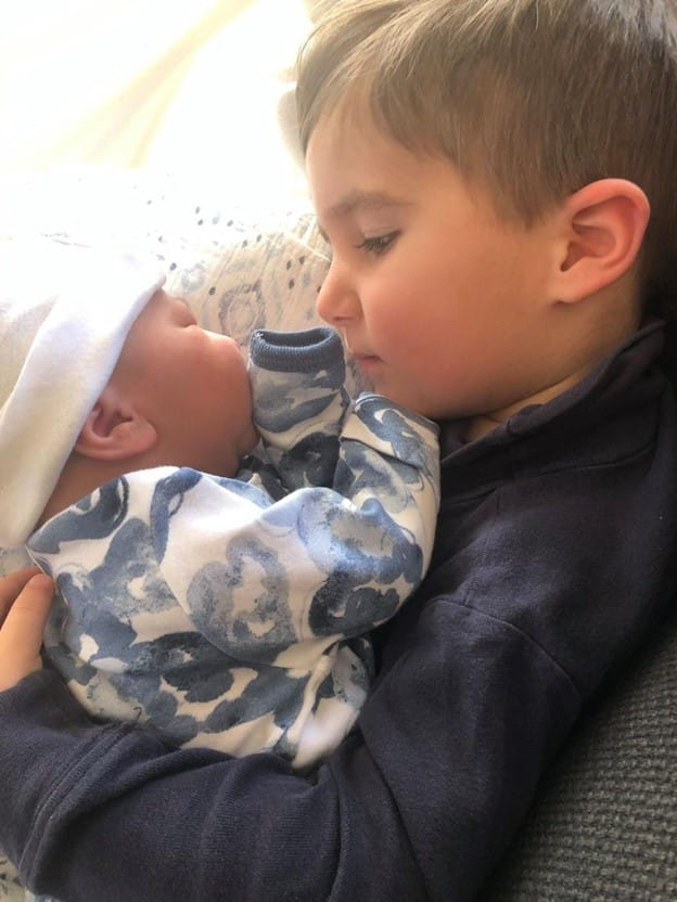older sibling holding new baby