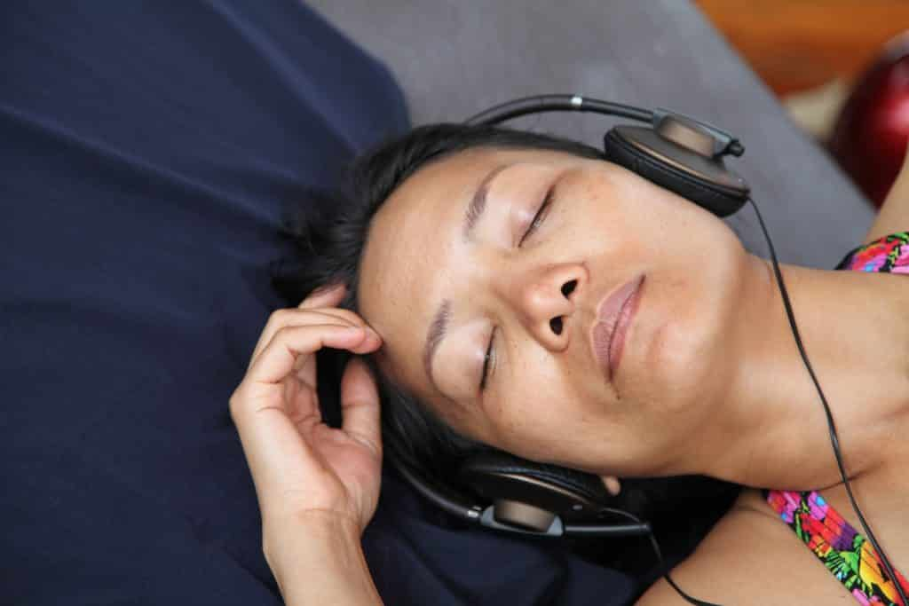 relaxed woman enjoying listening to hypnosis with headphones closed eyes