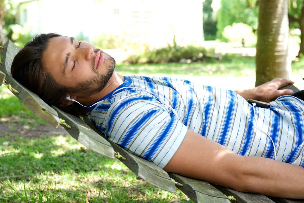 Man Lying in a hammock with headphones on
