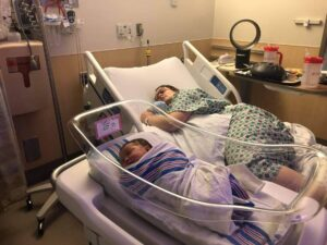 New parent sleeping in hospital bed with new baby sleeping nearby in bassinet