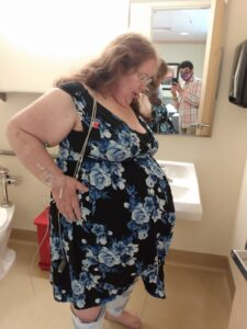 Pregnant person standing in bathroom waiting for c-section