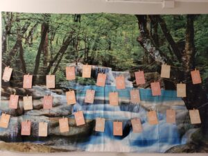 Birth affirmations hanging on a wall with a mural of forest and waterfall