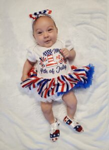 New baby dressed in 4th of July shirt and skirt