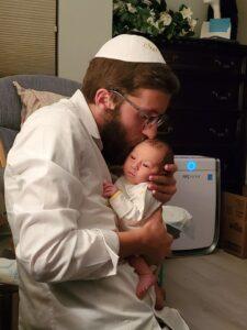 New parent kissing newborn on the head