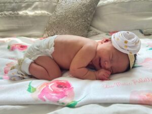 Newborn baby laying on tummy on flowered blanket