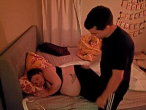 Pregnant person laying in bed with partner giving massage
