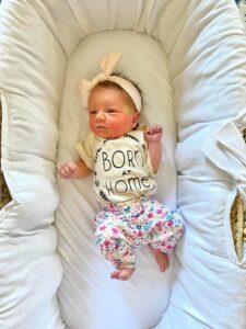 Newborn baby in bassinet wearing a born at home onesie