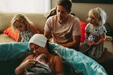 birthing person holding newborn in birth tub with family watching