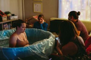 birthing person in birth tub with birth team watching