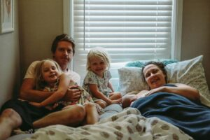 New family in bed after birth of newborn