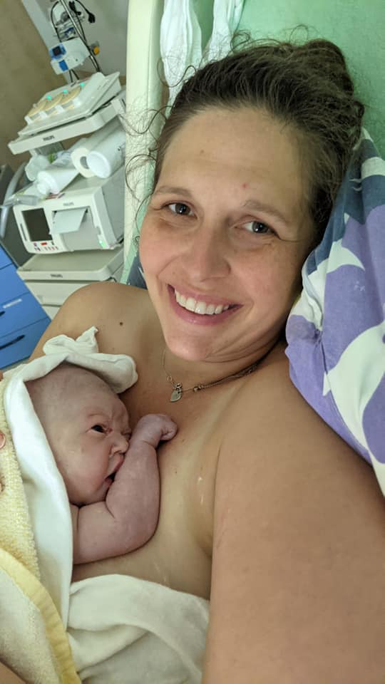 New parent holding newborn skin to skin and smiling